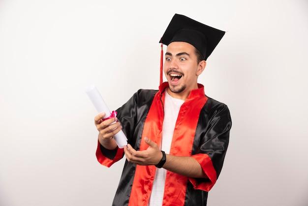 Jonge afgestudeerde student die zich gelukkig voelt voor het ontvangen van zijn diploma op wit.