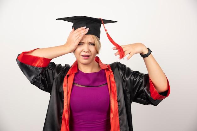 Jonge afgestudeerde student in jurk met hoofdpijn op witte muur.