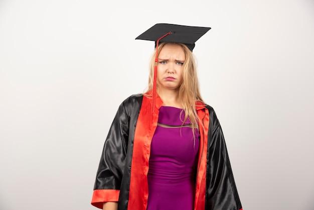 Jonge afgestudeerde student in jurk verdrietig op witte muur.
