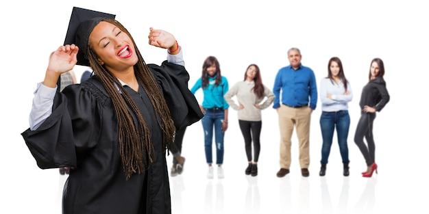 Jonge afgestudeerde zwarte vrouw met vlechten luisteren naar muziek, dansen en plezier maken