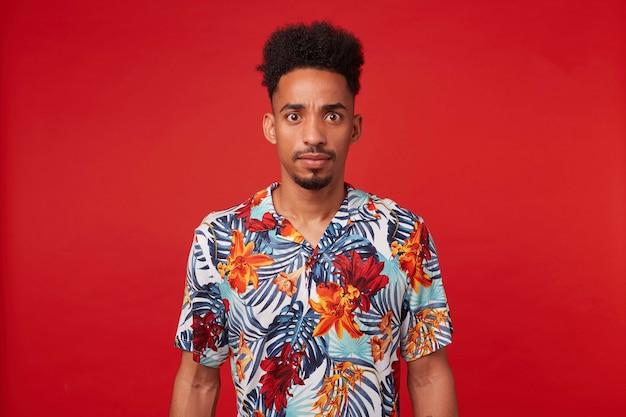 Jonge afgevraagd afro-amerikaanse man, draagt in een hawaiiaans shirt, kijkt naar de camera met verbaasde uitdrukking en wijd geopende ogen, staat op een rode achtergrond.