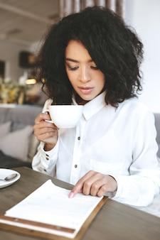 Jonge african american dame zittend in restaurant met kopje koffie in de hand en bedachtzaam