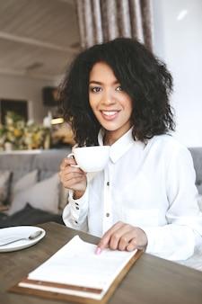 Jonge african american girl, zittend in restaurant met kopje koffie