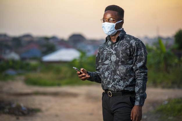 Jonge african american man draagt een beschermend gezichtsmasker met zijn telefoon buitenshuis