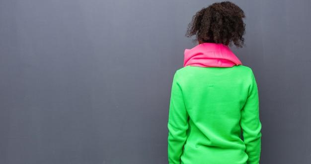 Jonge african american meisje met blauwe ogen van achteren, terugkijkend