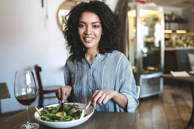 Jonge african american meisje met donker krullend haar zittend in restaurant