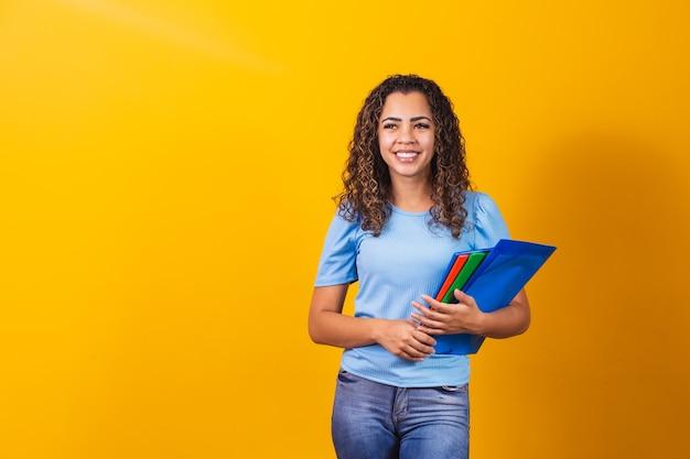 Jonge african american tiener student in casual kleding met boeken geïsoleerd op gele achtergrond studio portret. onderwijs op middelbare school universiteit college concept. mock-up kopie ruimte