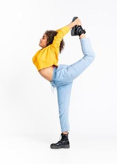 Jonge african american vrouw dansen op witte muur