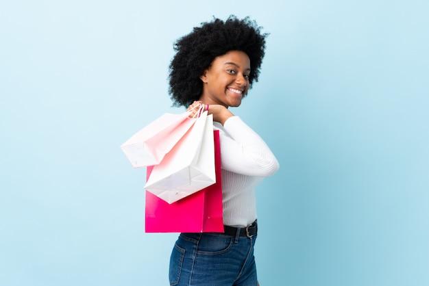Jonge african american vrouw geïsoleerd op blauw bedrijf boodschappentassen en lachend
