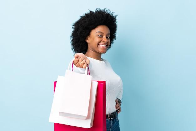 Jonge african american vrouw geïsoleerd op blauwe boodschappentassen houden en geven ze aan iemand
