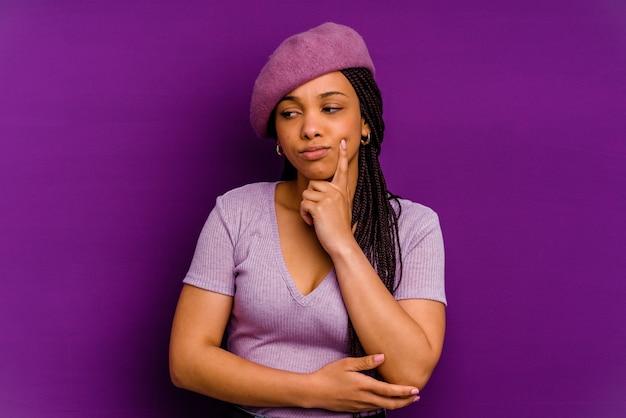 Jonge african american vrouw geïsoleerd op gele achtergrond jonge african american vrouw geïsoleerd op gele achtergrond overweegt, een strategie plannen, na te denken over de manier van een bedrijf.