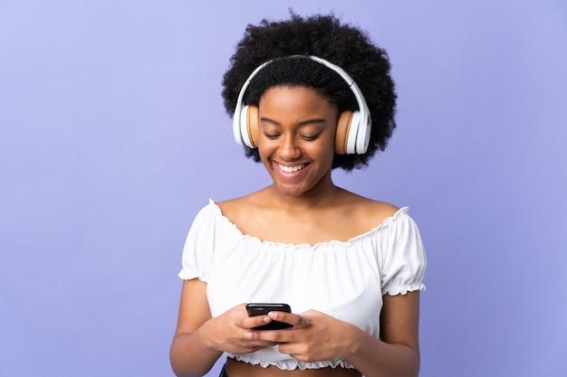 Jonge african american vrouw geïsoleerd op paarse achtergrond muziek luisteren en op zoek naar mobiel