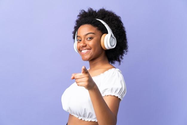 Jonge african american vrouw geïsoleerd op paarse achtergrond muziek luisteren en wijst naar de voorkant