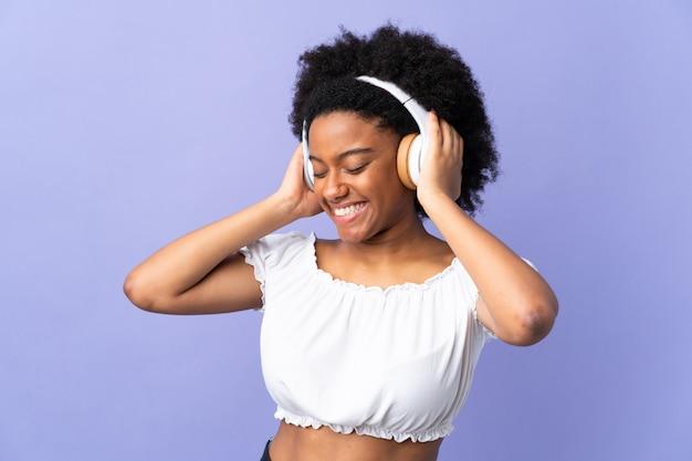 Jonge african american vrouw geïsoleerd op paarse muziek luisteren