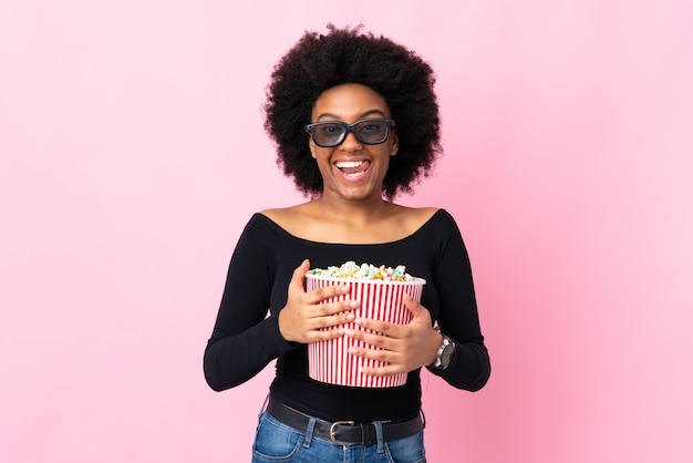 Jonge african american vrouw geïsoleerd op roze achtergrond met 3d-bril en met een grote emmer popcorns