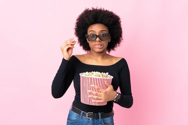 Jonge african american vrouw geïsoleerd op roze met 3d-bril en met een grote emmer popcorns