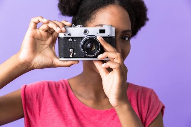 Jonge african american vrouw glimlachend en fotograferen op retro camera, geïsoleerd