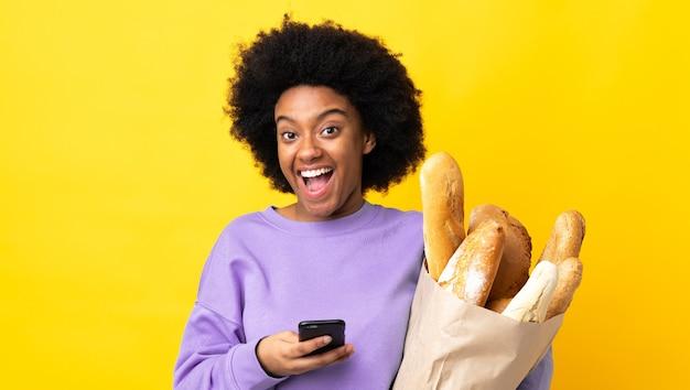 Jonge african american vrouw iets brood kopen geïsoleerd op geel verrast en een bericht verzenden