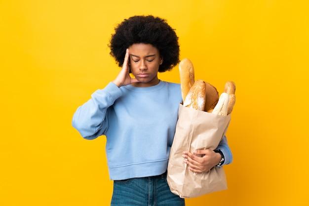 Jonge african american vrouw iets brood kopen geïsoleerd op gele achtergrond met hoofdpijn