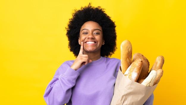 Jonge african american vrouw iets kopen brood geïsoleerd op geel lachend met een gelukkige en aangename uitdrukking