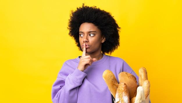 Jonge african american vrouw iets kopen brood geïsoleerd op geel met een teken van stilte gebaar vinger in de mond