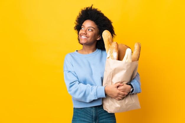 Jonge african american vrouw iets kopen brood geïsoleerd op geel opzoeken tijdens het glimlachen
