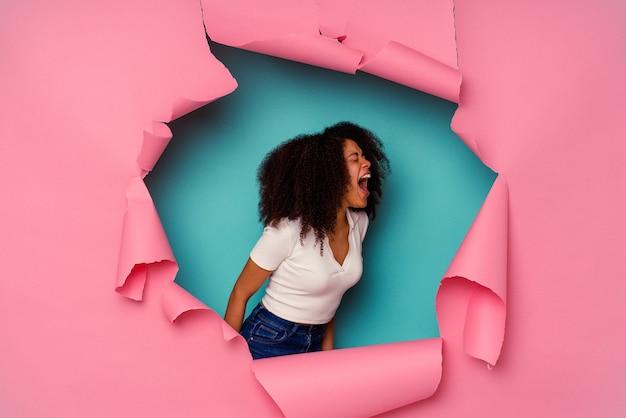 Jonge african american vrouw in gescheurd papier geïsoleerd op blauwe achtergrond schreeuwen naar een kopie ruimte