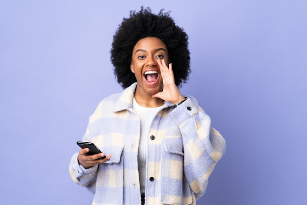 Jonge african american vrouw met behulp van mobiele telefoon geïsoleerd op paars schreeuwen met wijd open mond