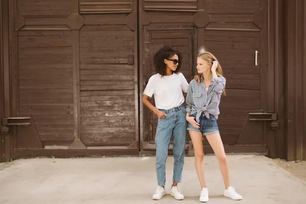Jonge african american vrouw met donker krullend haar in zonnebril en t-shirt en mooie vrouw met blond haar in shirt zorgvuldig op zoek opzij tijd samen buiten doorbrengen