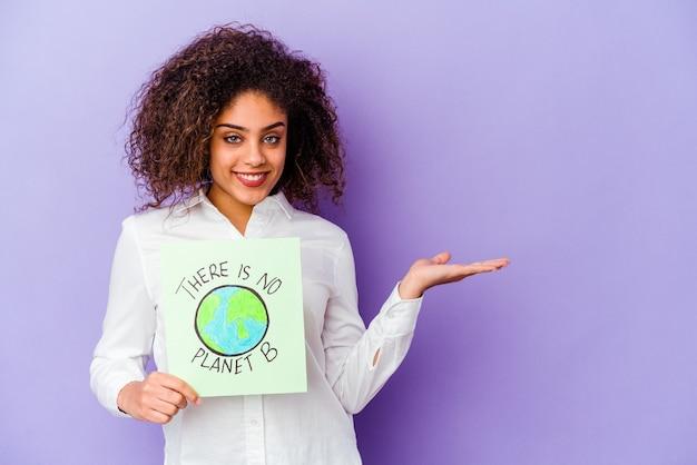 Jonge african american vrouw met een er is geen planeet b plakkaat geïsoleerd met een kopie ruimte op een palm en met een andere hand op de taille.