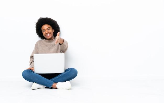 Jonge african american vrouw met een laptop zittend op de vloer handen schudden voor het sluiten van een goede deal