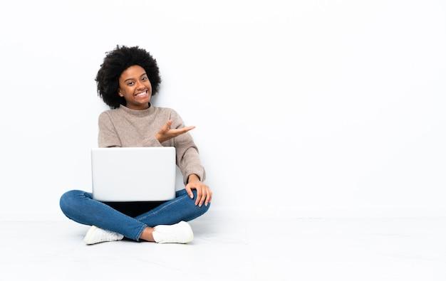 Jonge african american vrouw met een laptop zittend op de vloer presenteert een idee terwijl op zoek naar glimlachen