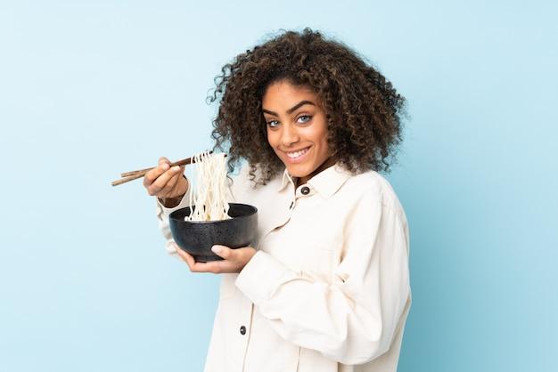 Jonge african american vrouw op blauwe muur met een kom noedels met stokjes