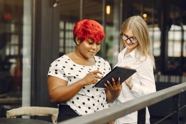 Jonge african american vrouw werkt in een kantoor. dame in een witte blouse. blanke vrouw met haar afrikaanse collega.