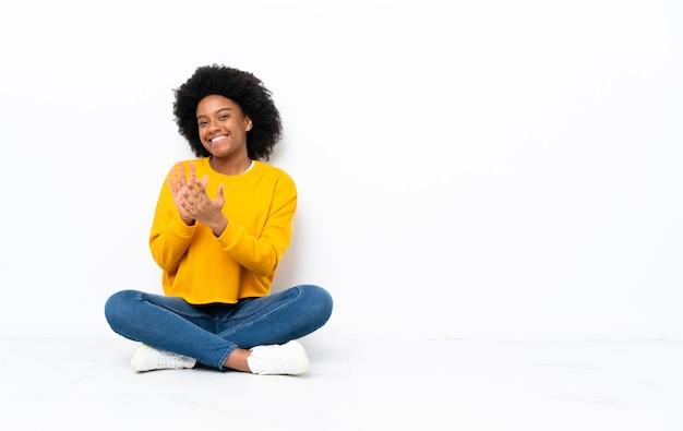 Jonge african american vrouw zittend op de vloer applaudisseren na presentatie in een conferentie
