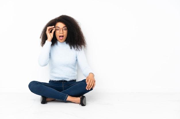 Jonge african american vrouw zittend op de vloer met een bril en verrast