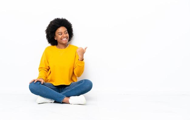 Jonge african american vrouw zittend op de vloer wijst naar de zijkant om een product te presenteren