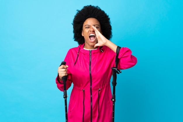 Jonge afrika amerikaan met rugzak en trekkingstokken op blauwe muur die en iets schreeuwen aankondigen