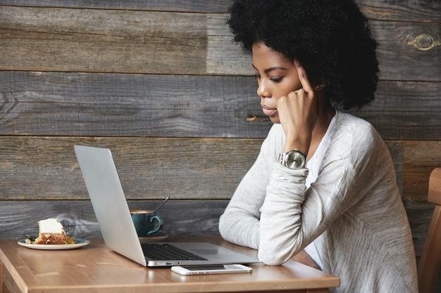 Jonge afrikaans-amerikaanse vrouw die laptop met behulp van