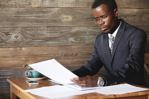 Jonge afrikaanse accountant die formele kleding draagt, documenten vasthoudt en zich met papierwerk bezighoudt