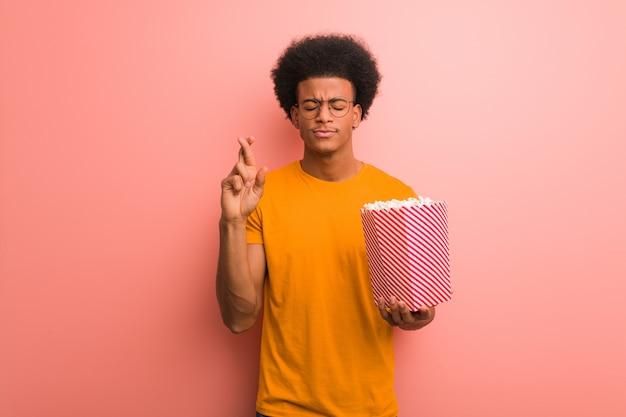 Jonge afrikaanse amerikaan die een popcornemmer houdt die vingers kruist voor het hebben van geluk