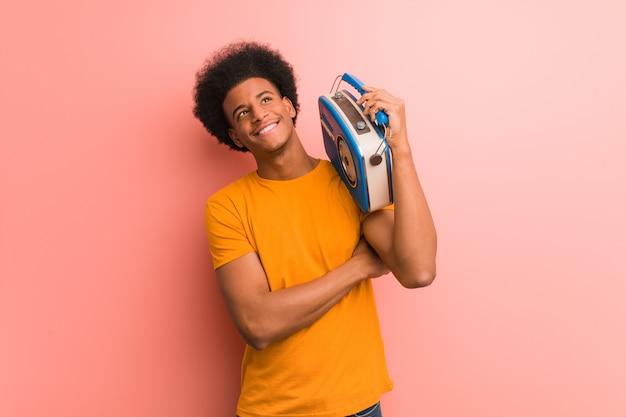 Jonge afrikaanse amerikaan die een uitstekende radio houdt die zekere en wapens glimlacht kruist, die omhoog eruit ziet