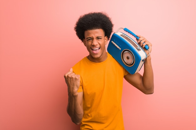 Jonge afrikaanse amerikaan die een uitstekende verrast en geschokte radio houden