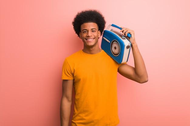 Jonge afrikaanse amerikaan die een vintage radio vrolijk met een grote glimlach houdt