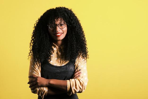Jonge afrikaanse amerikaan met afrokapsel, oogglazen en gele achtergrond