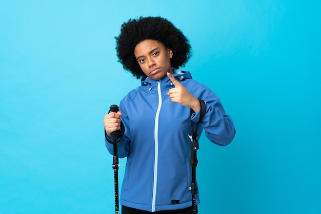 Jonge afrikaanse amerikaan met rugzak en trekkingstokken die op gefrustreerd blauw worden geïsoleerd en naar voren wijzen