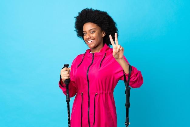 Jonge afrikaanse amerikaan met rugzak en trekkingstokken geïsoleerd op blauw glimlachend en overwinningsteken tonen