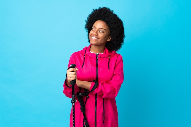 Jonge afrikaanse amerikaan met rugzak en wandelstokken geïsoleerd op blauw opzoeken tijdens het glimlachen