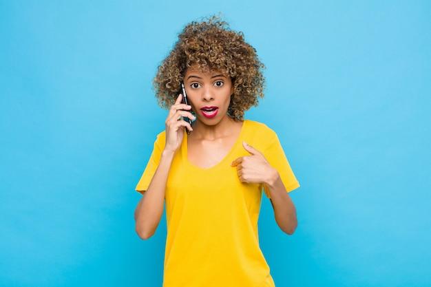 Jonge afrikaanse amerikaan op zoek geschokt en verrast met wijd open mond, wijzend naar zichzelf met een mobiele telefoon