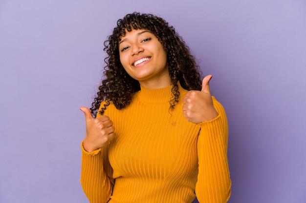 Jonge afrikaanse amerikaanse afro geïsoleerde vrouw die beide duimen opheft, glimlachend en zelfverzekerd.